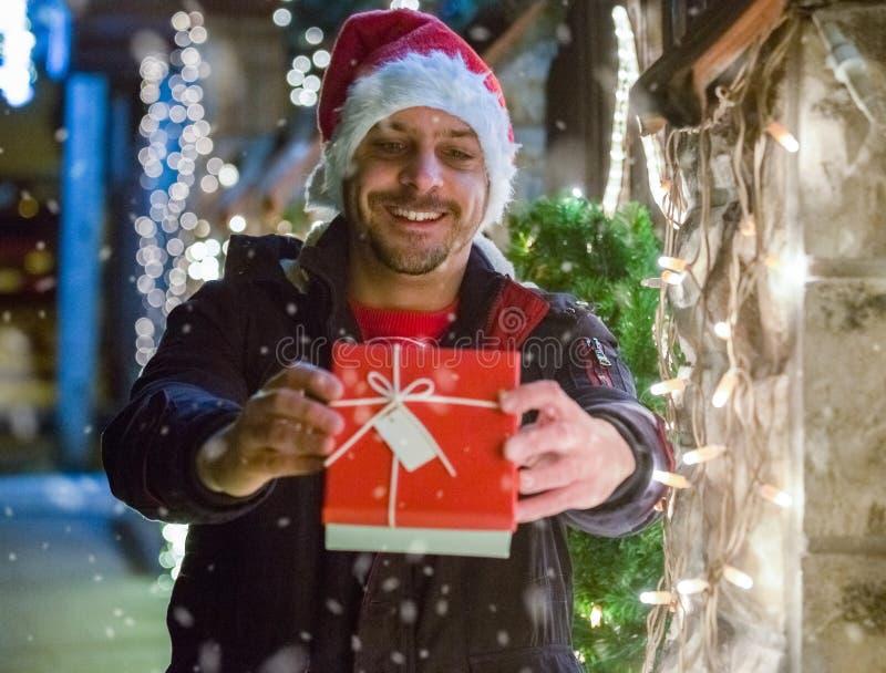 Stående av den unga le mannen i gåva för jultomtenhattinnehav därefter arkivfoton