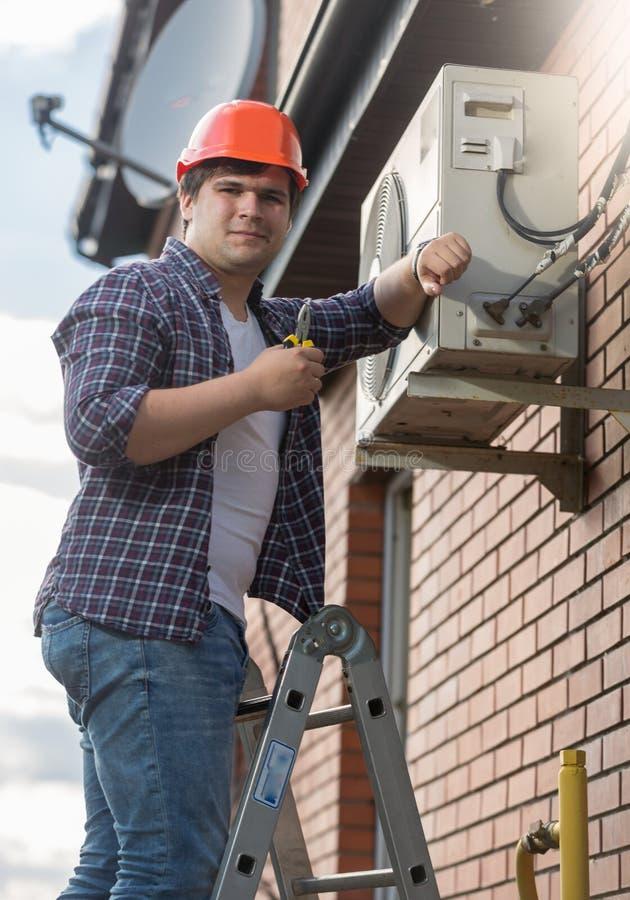Stående av den unga luftkonditioneringsapparatteknikern som kontrollerar det betingande systemet arkivfoton