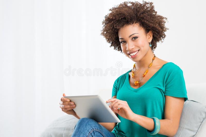 Afrikansk kvinna som använder den Digital tableten arkivfoton