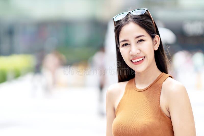 Stående av den unga lyckliga attraktiva asiatiska kvinnan som ler till kameran på stadsbakgrund i begrepp av skärmen för sol för  fotografering för bildbyråer