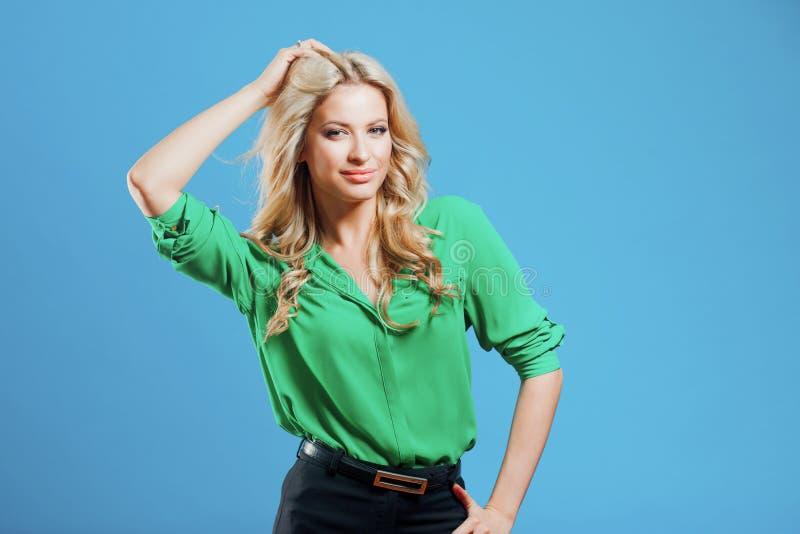 Stående av den unga lyckliga blondinen, tillfällig stil, blå bakgrund royaltyfri bild