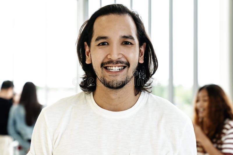 Stående av den unga lyckliga korta stilfulla skäggiga asiatiska mannen eller det idérika märkes- leendet och att se kameran arkivbild