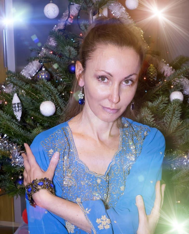 Stående av den unga lyckliga kvinnan mot ett träd för ` s för nytt år royaltyfri fotografi