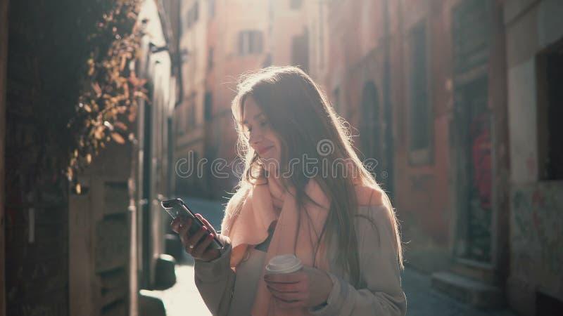 Stående av den unga lyckliga kvinnan som går i stad och använder smartphonen Flickabläddrande internet och drickakaffet royaltyfri fotografi