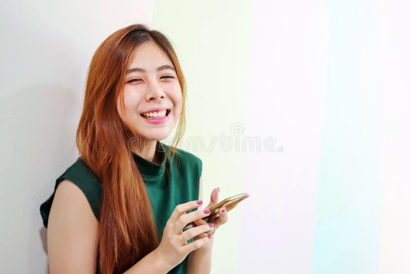 Stående av den unga lyckliga kvinnan som ser kameran med att charma leende, medan genom att använda en smart telefon arkivfoto