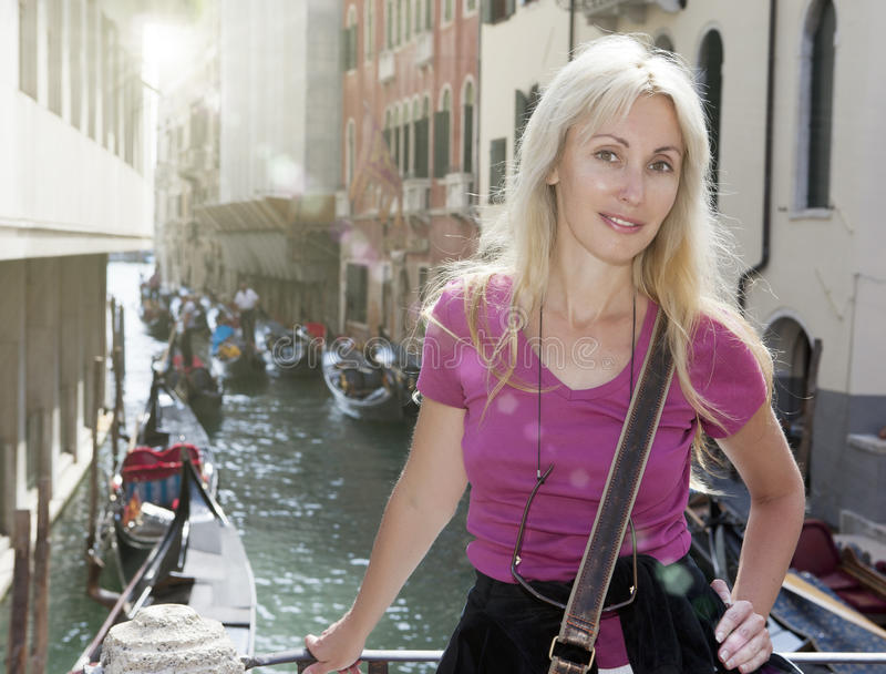 Stående av den unga lyckliga kvinnaturisten på kanalbakgrunden i Venedig arkivfoto