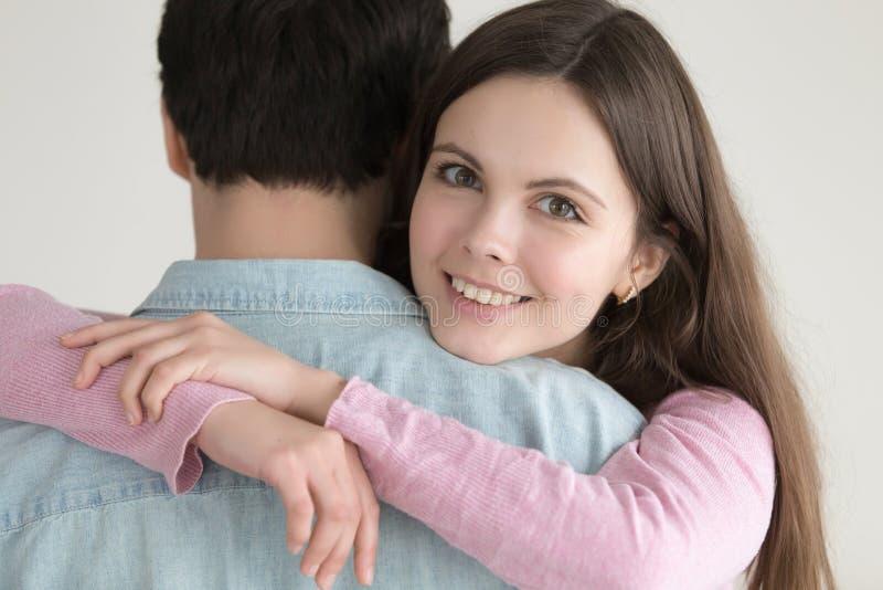Stående av den unga lyckliga le kvinnan som kramar mannen med förälskelse arkivfoto