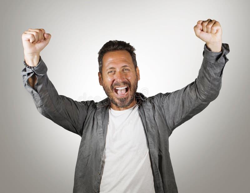 Stående av den unga lyckliga och attraktiva Caucasian mannen som gör en gest med näven som lyfter armar, i att le för seger- och  arkivbild