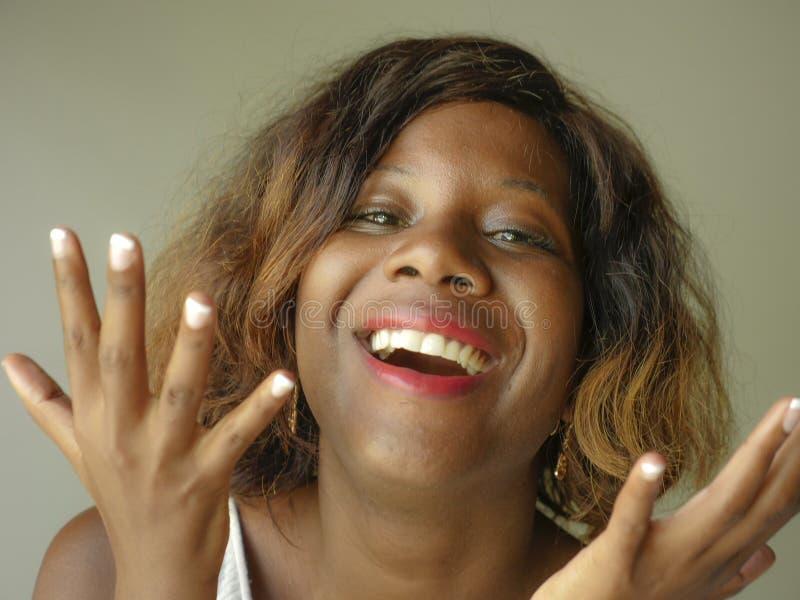 Stående av den unga lyckliga och härliga svarta afrikansk amerikankvinnan som poserar charmigt och skämtsamt le gladlynt se till royaltyfri bild