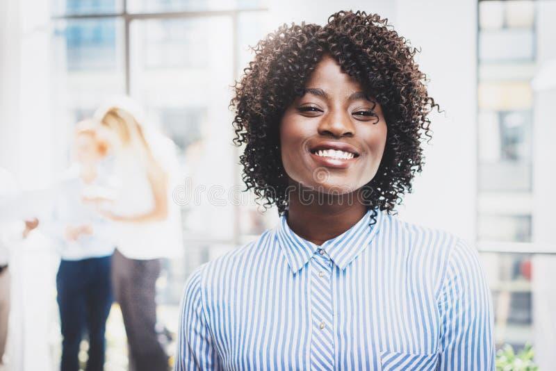 Stående av den unga lyckliga svarta kvinnliga kontorsarbetaren i modern coworking studio med affärslaget på bakgrunden royaltyfria bilder