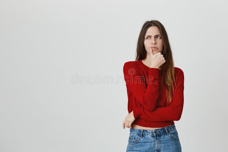 Stående av den unga magra kvinnlign i moderiktig kantjusterad överkant som rymmer handen på hakan med eftertänksamt och koncentre royaltyfri bild