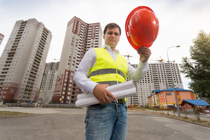 Stående av den unga manliga arkitekten som rymmer den röda plast- hardhaten på byggnadsplats royaltyfria bilder