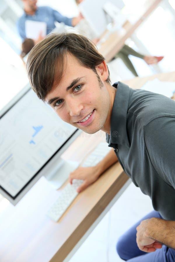 Stående av den unga manliga studenten som arbetar på datoren arkivbild