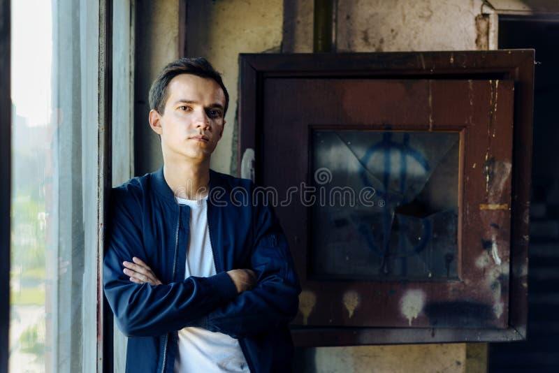 Stående av den unga mannen i omslagsställningar nära fönster och den brutna asken royaltyfria foton