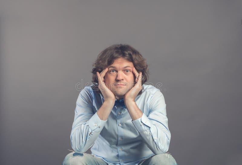 Stående av den unga mannen i studio som vilar hakan på händer, medan sitta och utvilade armbågar på knä Öppna ögon vitt och att s royaltyfri bild