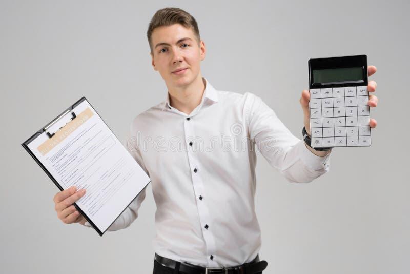 Stående av den unga mannen med formen av betalning av räkningar och räknemaskinen i hans händer som isoleras på vit bakgrund royaltyfri fotografi
