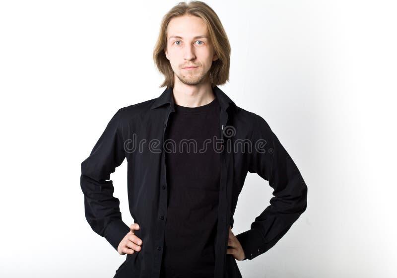 Stående av den unga mannen med långt blont hår, svart skjorta, vit b arkivfoto