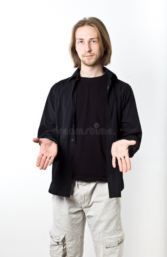 Stående av den unga mannen med långt blont hår, svart skjorta, vit b arkivbild