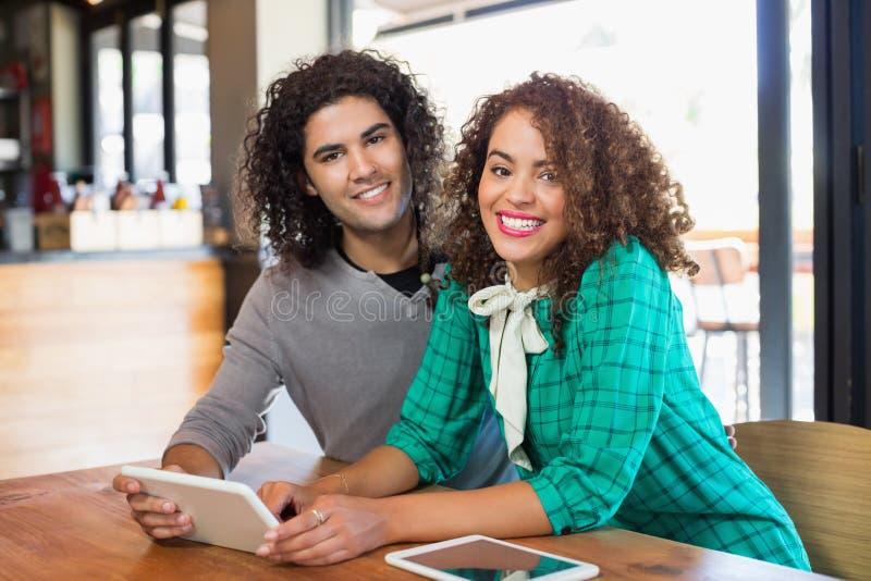 Stående av den unga mannen och kvinnan som använder den digitala minnestavlan royaltyfri fotografi