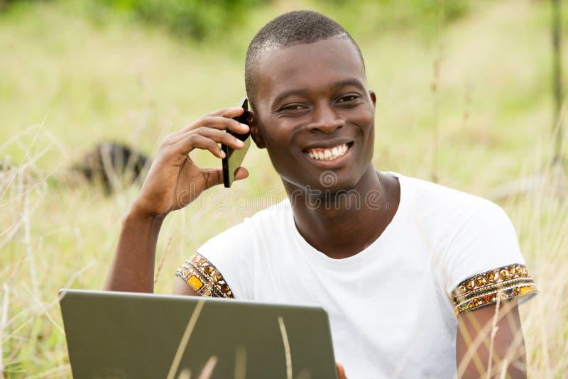 Stående av den unga mannen på mobiltelefonen som är lycklig fotografering för bildbyråer