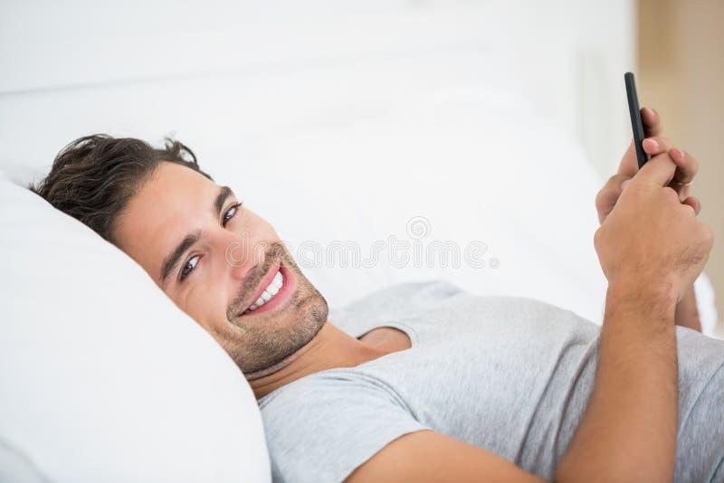 Stående av den unga mannen som använder mobiltelefonen på säng fotografering för bildbyråer