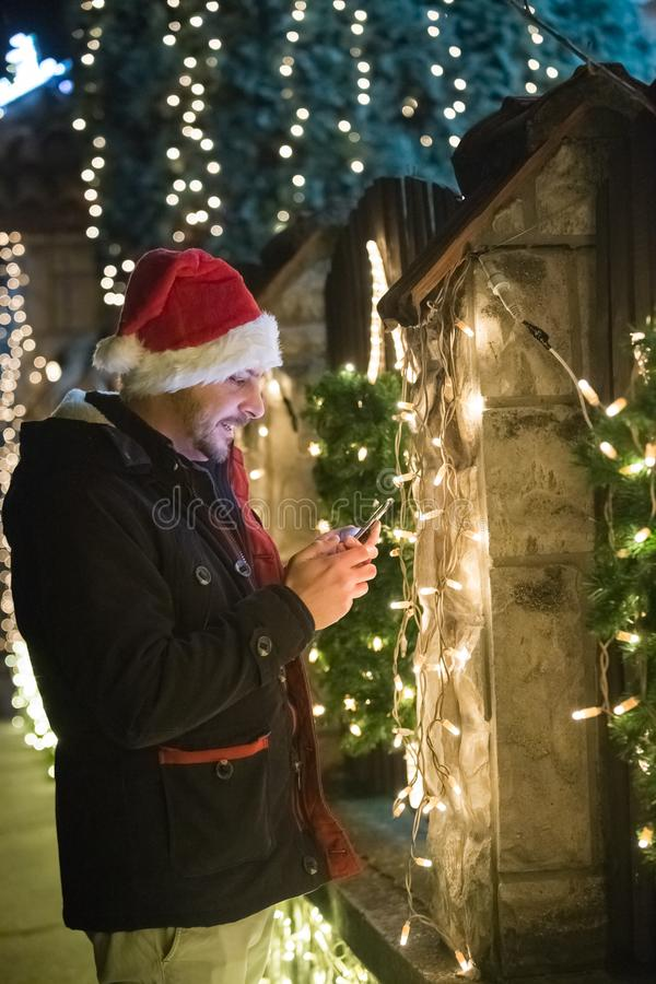 Stående av den unga mannen som som använder den smarta telefonen, med Santa Claus ca fotografering för bildbyråer