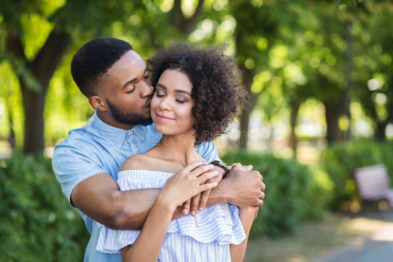 Stående av den unga mannen som kysser kvinnan i kind royaltyfri bild