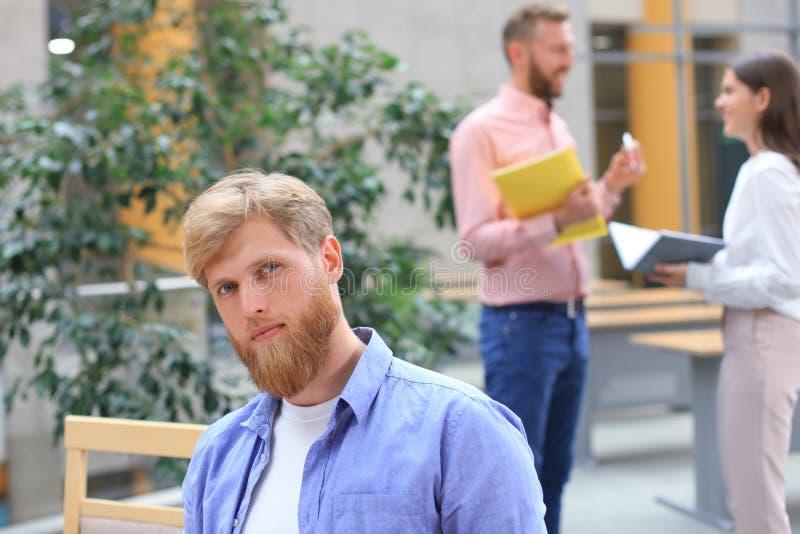 Stående av den unga mannen som sitter på hans skrivbord i kontoret som arbetar på hans PC royaltyfria bilder