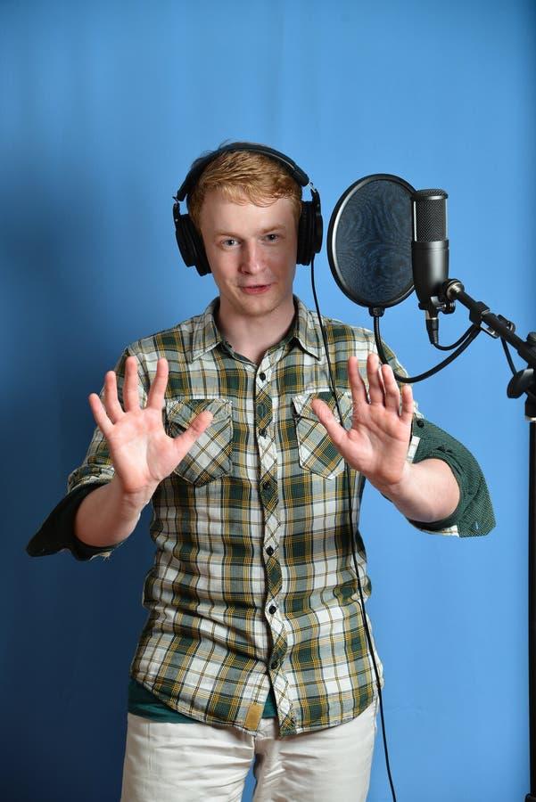 Stående av den unga mannen som sjunger in i mikrofonen royaltyfri bild