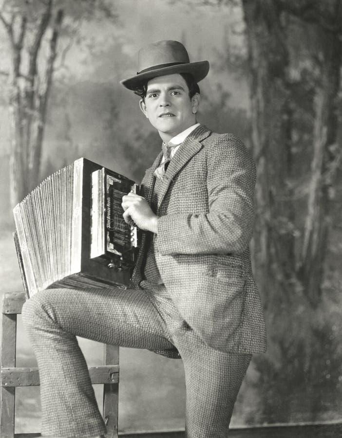Stående av den unga mannen som spelar dragspelet arkivbild