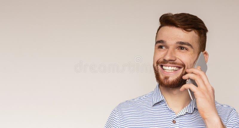 Stående av den unga mannen som talar på mobiltelefonen och att le arkivbild