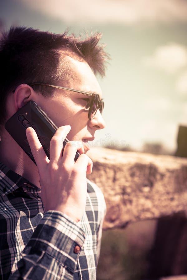 Stående av den unga mannen som talar vid telefonen tappning filtrerad bild fotografering för bildbyråer
