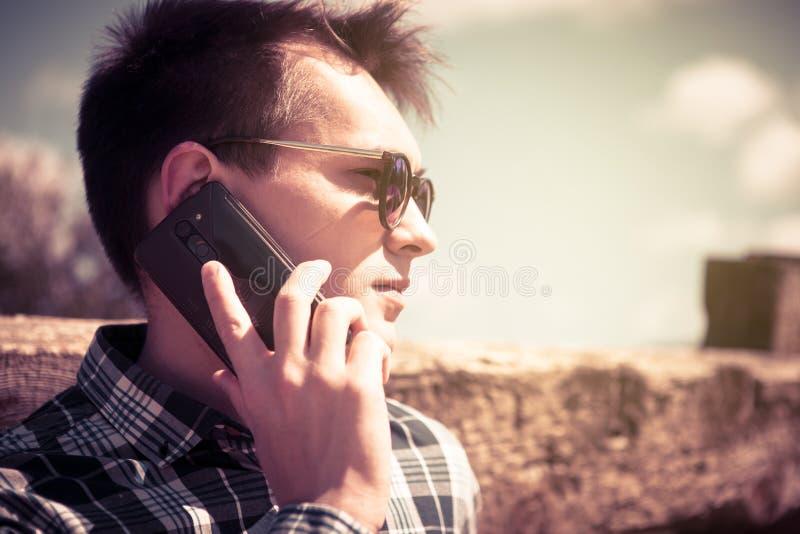 Stående av den unga mannen som talar vid telefonen tappning filtrerad bild royaltyfri bild