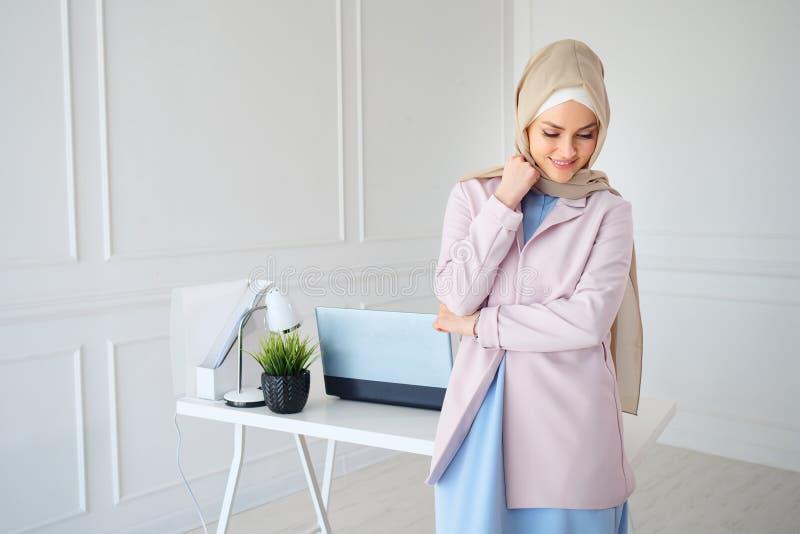 St?ende av den unga muslim kvinnan i beige hijab och traditionell kl?der som poserar i studio royaltyfri fotografi