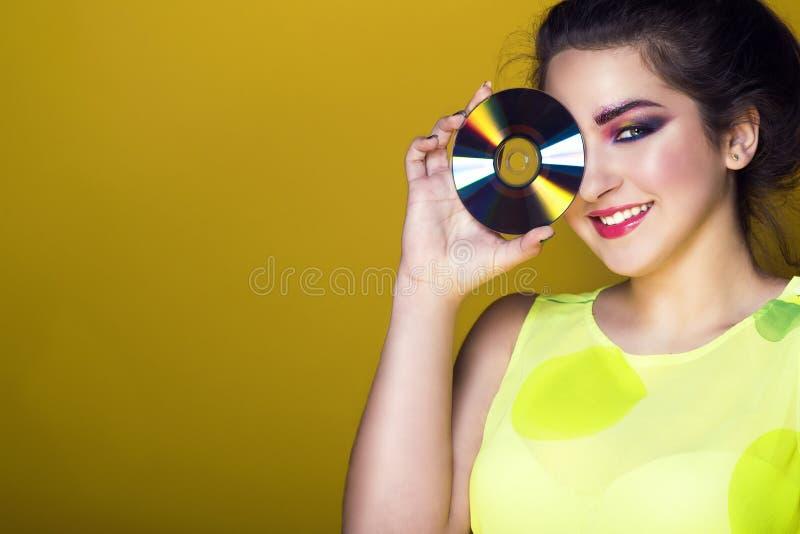 Stående av den unga nätta flickan med färgglat konstnärligt smink- och updohår som rymmer en CD främst av hennes öga och le arkivfoto