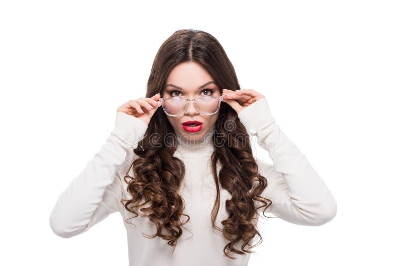 Stående av den unga nätta kvinnan med röd läppstift som ser över henne klara exponeringsglas, royaltyfri fotografi