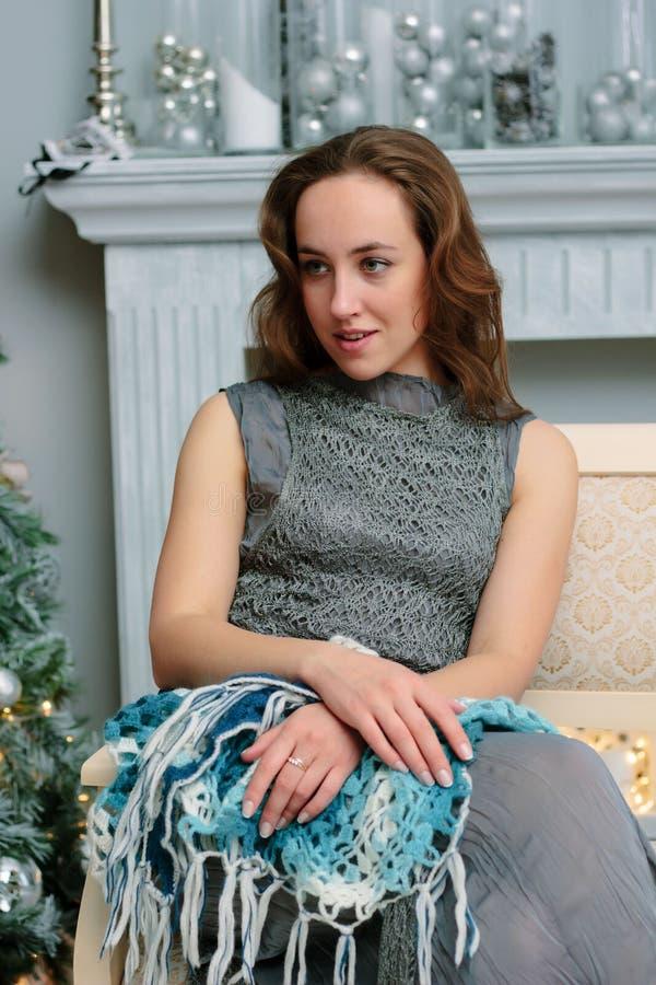 Stående av den unga och härliga flickan som sitter på soffan under julberöm arkivfoto