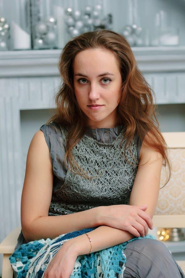 Stående av den unga och härliga flickan som sitter på soffan under julberöm arkivbild