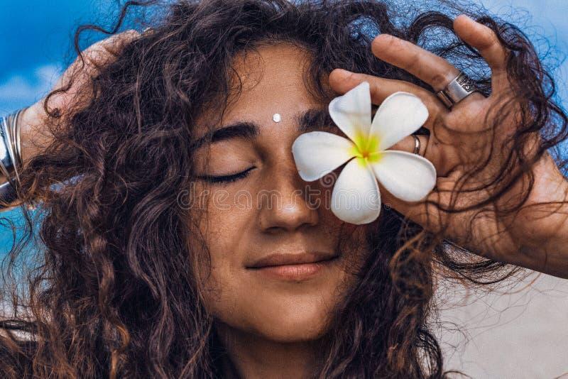 Stående av den unga och härliga gladlynta kvinnan med frangipaniblomman på stranden arkivfoton