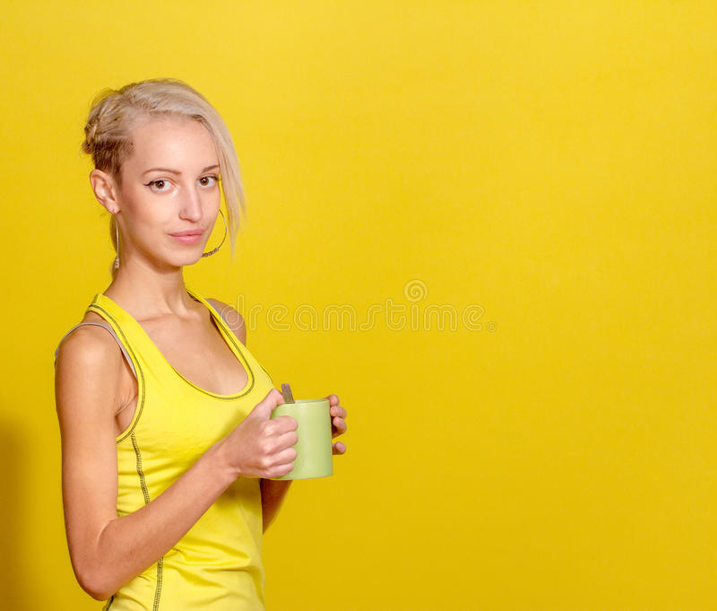 Stående av den unga och sunda blondinen med kopp te arkivfoton