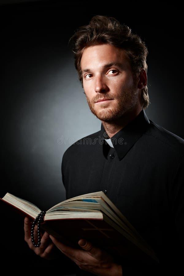 Stående av den unga prästen med bibeln. royaltyfria foton
