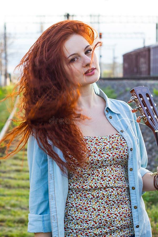 Stående av den unga rödhårig manflickan med gitarren arkivfoto