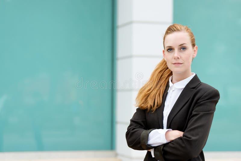 Stående av den unga säkra rödhårig manaffärskvinnan royaltyfri bild