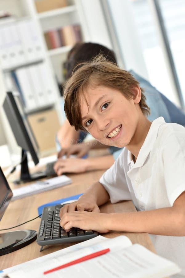 Stående av den unga skolapojken i klassrum arkivfoto