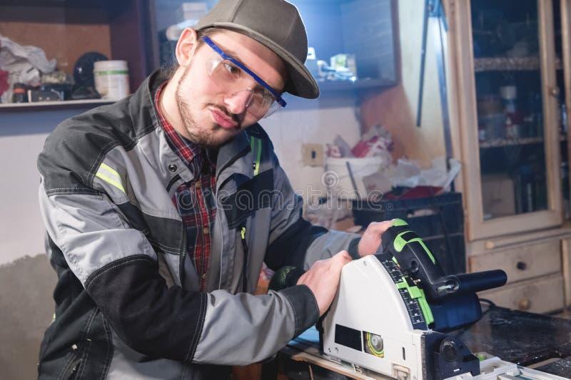 Stående av den unga snickaren för dilly som arbetar med en elektrisk nivå i ett hem- träseminarium Begreppet av en affär fotografering för bildbyråer