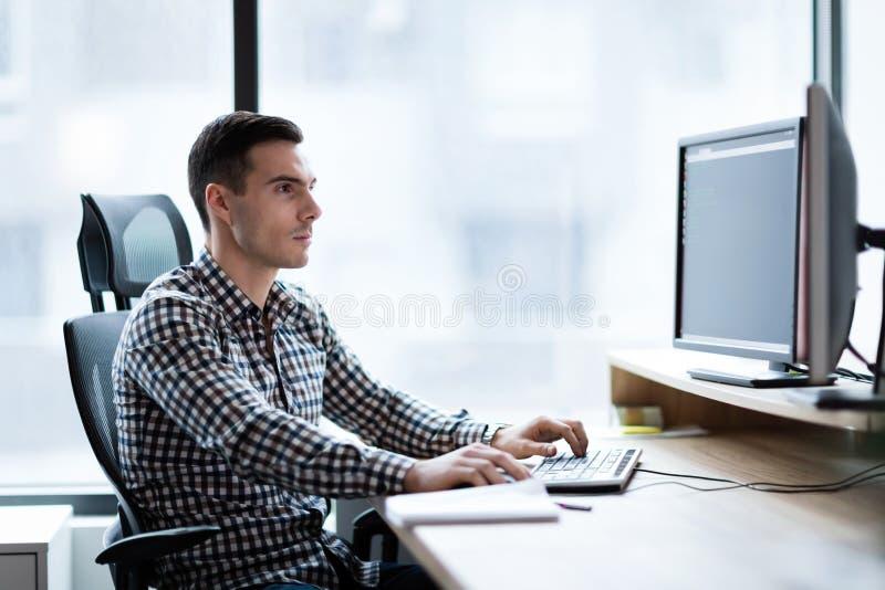 Stående av den unga stiliga affärsmannen som arbetar på datoren royaltyfria bilder