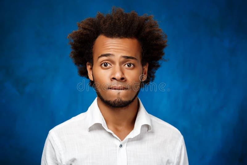 Stående av den unga stiliga afrikanska mannen över blå bakgrund arkivbild