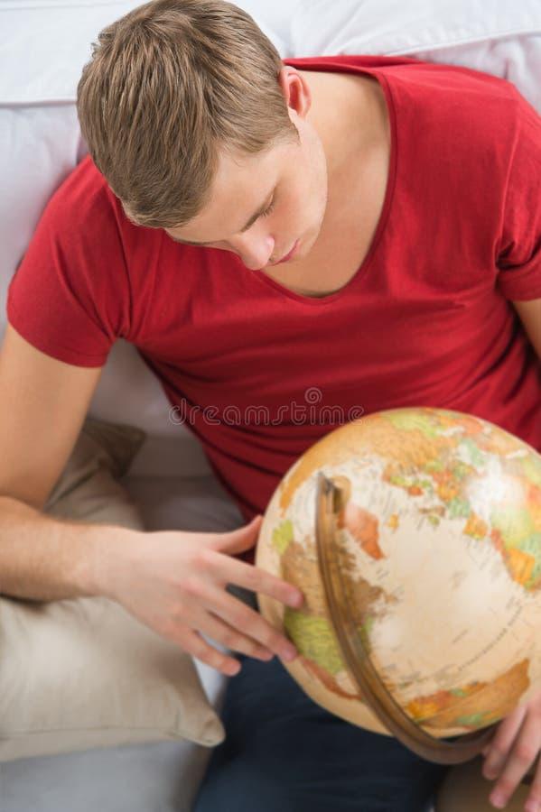 Stående av den unga stiliga caucasian mannen med jordklotet royaltyfri foto