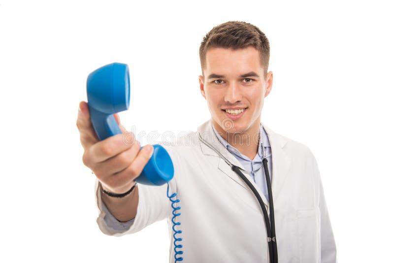 Stående av den unga stiliga doktorn som räcker den blåa telefonmottagaren royaltyfri foto