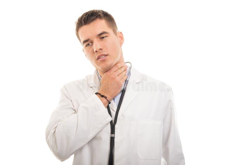 Stående av den unga stiliga doktorn som rymmer halsen som att göra ont arkivbilder